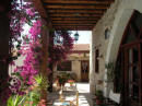Pretty bougainvillea and stone arches lend to the character of this addorable property